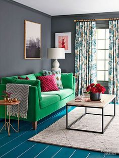 Charcoal gray walls, green sofa, and patterned curtains