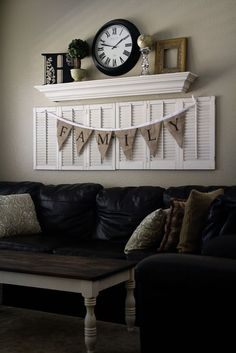 Living Room decor - rustic farmhouse style. Painted white shutters, floating shelf and gunnysack bunting.
