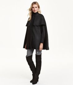 Cape in brushed, wool-blend bouclé fabric with a stand-up collar. Concealed snap fasteners at front, openings at sides for arms, and side pockets and storm flaps at front. Lined.