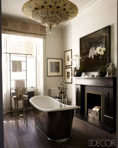 Fashion Editor Kim Hersov's Master Bathroom A tub with Lefroy Brooks fittings in the master bath; the towel stand is custom made, and the mantel is original to the house.