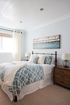 A white paneled ceiling adds an understated and stylish element to this bright bedroom. A long canvas mounted on the wall matches the blue of the patterned bedspread and pillow shams. The wrought iron bed frame is complemented by wrought iron trim on the wood side tables and wrought iron detailing on the lamp bases.