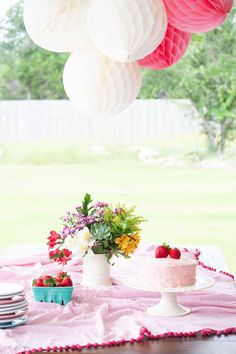 Farm-fresh flowers from The Bouqs are perfect here with strawberry cake, and pom pom tablecloth. Cool, outdoor feel for a Pretty in Pink Party.