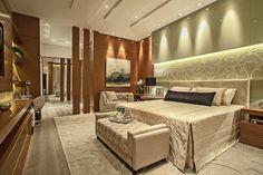 Neste lindo quarto a decoração é moderna e sofisticada, com muita madeira + tons de bege, off-white e azul marinho. A parede atrás da cama recebeu um painel de vidro + veludo estampado, com cabeceira também em tecido.