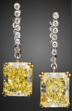 A pair of fancy colored diamond and diamond pendant earrings,            each designed a cut-cornered rectangular modified brilliant-cut fancy yellow diamond, each weighing 3.72 carats, suspended from a round brilliant-cut diamond line; mounted in platinum and eighteen karat gold; length: 1in. Via Bonhams.