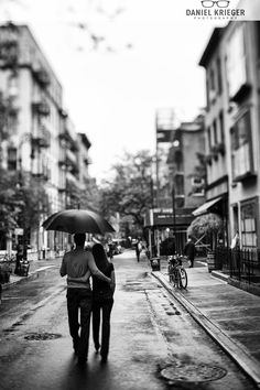 Back shot, arms around each other, she leaning on him and he's holding the umbrella