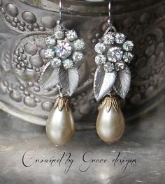Rhinestone silver floral pieces salvaged from vintage screw back earrings paired with shimmery champagne pearl drops. Hangs just over 1 1/2 inches from french ear wires.