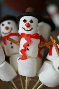 Traktatie sneeuwpop van marshmellows en zoute stokjes, oreo's en rolo's met een rode dropveter als sjaal.