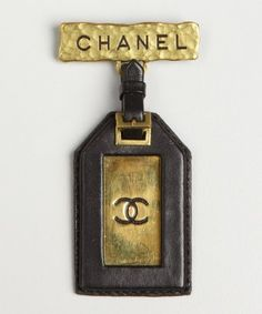 Chanel : gold and black metal and leather vintage luggage tag pin