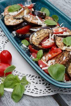 lækkert tilbehør til en varm aftenret.     Ingredienser (4 personer)  2 stk. aubergine 250 g cherrytomater 2 spsk. hvidløgsolie eller neutral olie 50 g revet parmesanost 1 tsk. oregano 1 tsk. basilikum Salt og peber