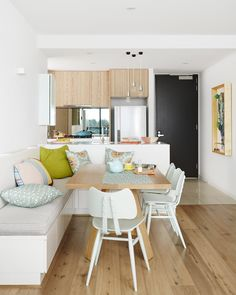 The kitchen and breakfast nook are ideal, with added storage that serves as multi-functional seating around a table. Top and bottom cabinets further maximise the space in the kitchen and we love the pops of colour that add to this space, from aqua pots on the stove to the pastel mix of scatters. These pair well with the timber tones of the flooring and oak cabinets.