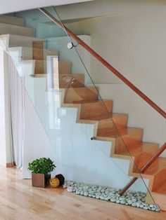 Such a unique glass stair rail! Love that in isn't completely attached to hand rail - stones underneath!! NEED