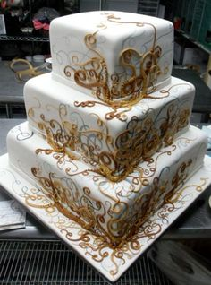 Cool three tier square wedding cake with golden swirls that look very squid-like...