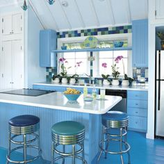 Colorful Kitchen:  Waves of blue drench this kitchen. A pale shade covers the walls and ceiling while a deeper shade is used on the cabinets. The wood floors carry a third shade of blue. Such colors are a perfect reflection of the nearby Gulf of Mexico waters.  via Southern Living