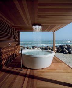Bathroom Designs. Gorgeous Zucchetti Kos Geo 180 freestanding bathtub in outdoor wooden bathroom with amazing ocean view.