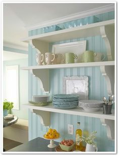 Beautiful white shelving against a blue beadboard wall.