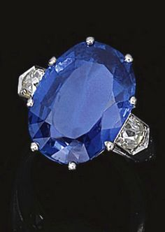 SAPPHIRE AND DIAMOND RING, CHAUMET, CIRCA 1930 Claw-set with an oval sapphire, flanked by cushion-shaped diamonds, mounted in platinum, size 50½, unsigned, French assay and maker's marks.
