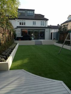 ein künstlicher Gras Rasen, Bäume an den Zaun, Haus im minimalistischem Stil Gartengestaltung Beispiele