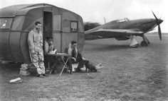 "F/L Henry M ""Mike"" Ferriss (left) of No 111 Squadron RAF waits at readiness outside a caravan on dispersal at RAF Wick alongside Hurricane Mk I JU-K in 1940. On 18 May, the 22-year-old pilot claimed success against 3 Me 110 fighters and probably another, but admitted having shot a crew on their parachutes after seeing them bailing out and clearly falling in enemy-held territory. He was awarded a DFC on 21 June for 7 recorded victories."