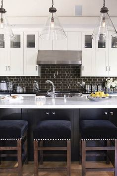 crisp rich masculine colors kitchen design black velvet nailhead backless barstools glass pennant lights white cabinets wall cabinets dual  panel wall cabinet design dark subway tile backsplash