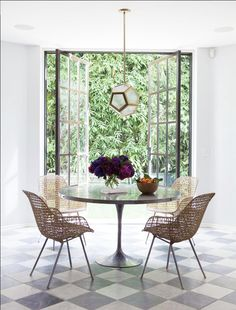 Dining space with white walls, marble floors, brass light fixture, and large glass doors showing outdoor bamboo