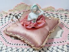Vintage Glazed Porcelain Half Doll Pink Pincushion with Our Ladys Boudoir Pincushion Original Label. This open armed or half away arms half doll has a green headband and an iridescent pink rayon ribbon skirt. She is embedded in a soft square shaped pink satin pincushion with ruffled contrasting pink silk ribbon around the perimeter.  In lovely vintage condition with normal pin prick holes and some light stains in the satin. The porcelain figurine has no chips or cracks and is beautifully…