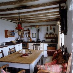 A brass oil lamp hangs from the beamed ceiling above the table in the kitchen. All the oak rafters and beams are original.