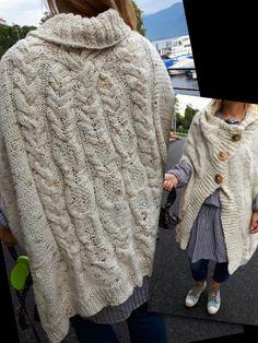 Mantellina di lana con lavoro a trecce sul retro e bottoni di legno per chiudere il davanti