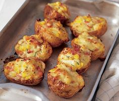 Baked potatoes on a baking tray, stuffed with ham cheese and egg