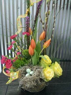 Spring arrangement of pussy willow,  roses,  green trick dianthus,  mini carnations,  and tulips. Finished with a birds nest, and eggs.