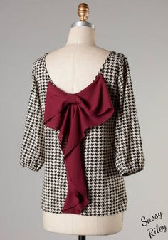 Black and white houndstooth print bow back top that is sweet and feminine. The burgundy bow adds a touch that takes this top from cute to over the top adorable. The houndstooth print is perfect for game day with the black and white print and big burgundy bow. 3/4 sleeve is banded with elastic at the bottom, with a loose and easy fit. Wear this cute top with dark denim jeans and flats.