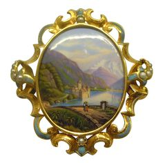 "Château de Chillon Swiss Enamel Gold Brooch, Circa 1880 Switzerland 19th Century Swiss Enamel, Pearl and Gold Mounted Brooch, Circa 1880. The central enamel plaque depicts the Chateau de Chillon amidst the Swiss Alps in beautiful realistic subtle hues. The gold frame is engraved and set with several pearl sections alternating with sections of enamel (minor traces of loss to enamel). The back of the brooch is enameled in a pale blue hue and signed ""Chillone"" for the Château de Chillon.3800"