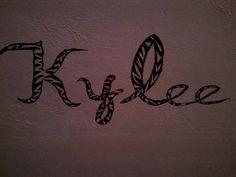 Kylee's name hand-painted in zebra print on her bedroom wall.