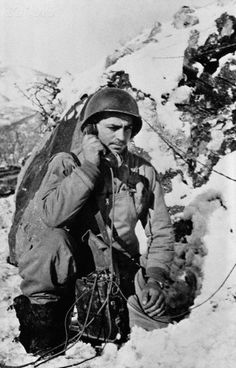 A U.S. soldier of the Allied Fifth Army fighting the Germans in western Italy repairs a telephone line broken during a snow storm, Ca. 1944. #Italy #WWII #War