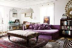 Bohemian Vintage Living Room: A purple couch and layered rugs in a living space.