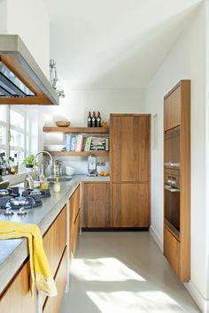 reforma cocina planta alargada con muebles de madera, encimera y suelo de microcemento.