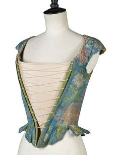 early 1700s - A LADY'S SILK CORSET - FRANCE, EARLY 18TH CENTURY brocaded with flowers against a powder blue ground, with numerous tabs edged with braid