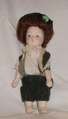 A little china or bisque costume doll. I think it is Irish and the clothes are velvet and silk, It's a boy as he's wearing knee breeches he's, anyway he's stay'n.