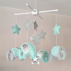 Elephant and stars baby crib mobile. An ideal gift for a new babys nursery or for room decor in an older childs bedroom. This mobile consists of four beautiful elephants in pale grey and mint green with lovely big floppy ears in mint and silver. It also has six stars in colours to match the elephants and a fluffy white cloud in the centre. The elements are suspended with white thread from either a natural wood or a white wooden mobile hanger. Each element is created with felt and entirely…