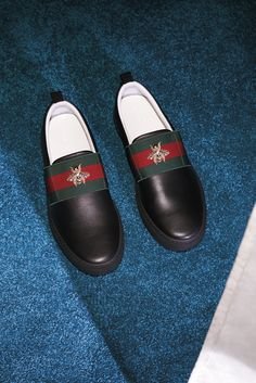 Sneakers from the Gucci Gift selection: slip-ons in black leather detailed with a signature green-red-green Web stripe and embroidered gold bee from the Gucci Cruise 2016 collection by AlessandroMichele.