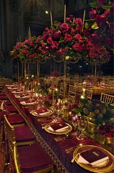 A long table is decorated with candelabra covered in red roses and low arrangements of flowers and fruit.