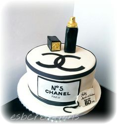 Classy black and gold Chanel cake with perfume bottle.