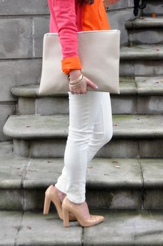 White jeans with orange and pink tops, nude accessories.