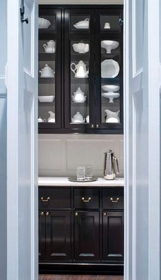 Glossy black butler's pantry with white marble counters and gray inside glass-front upper cabinets