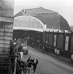 Elevated view looking down onto a roadway leading out of Paddington Station. The pavements are busy with pedestrians heading away from platform 9, which can be seen in the distance 60's