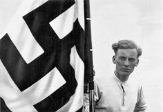 """A typical Nazi propaganda image of an Aryan youth with a Swastika flag proclaiming the future of Germany under the original caption: """"Our Banner Flies Before Us"""""""