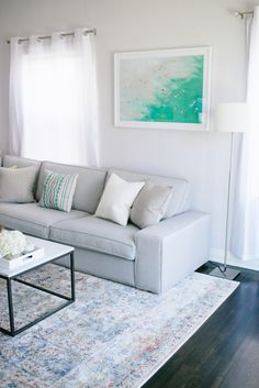 Cool Toned Living Room // Grey modern sofa, faded blue rug, white sheer curtains, west elm coffee table, ikea couch // clean, crisp, modern living room