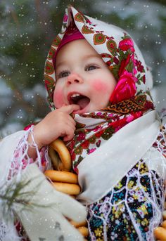 A cute little girl in the Russian traditional shawl with bright floral patterns.