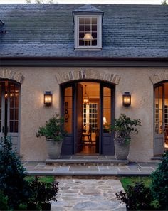 Lanterns, arched glass doors, exterior color and slate roof, stone planters, welcoming entrance, greys, black door