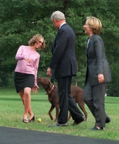 President Clinton watches and first lady Hillary Rodham Clinton, right, laughs as the Clinton's family dog Buddy tries to play ball with their daughter Chelsea after the family returned to the White House on Aug. 15, 2000 in Washington.