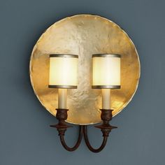 "Golden Nugget Plate Wall SconceHand-forged iron with a gold nugget finish gives this sconce Euro-heirloom style, kicked up a notch. The antiqued pearl glass shades trimmed in aged gold add an opera house elegance. A sconce for country chic to modern loft decor.  2-40 watt candelabra base lamps required. (14.75""Hx12""Wx5""D)"